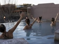 A group of women raising their arms in the water of the hot spring pool