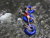 Three people floating on inflatable rings in the water