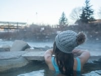 Woman soaking in a hot spring in winter